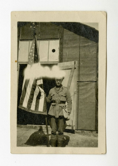 Walter Winthrop Gores, Sous Chef of SSU 70, standing with an American flag.