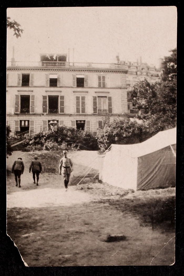 Three men next to a tent in the garden at 21 rue Raynouard